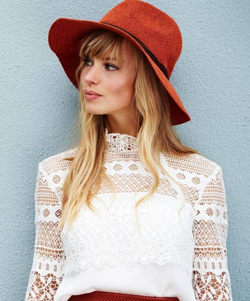 תמונה של אישה עם כובע כתום מצטלמת לאתר 131 בלוג אופנה לנשים