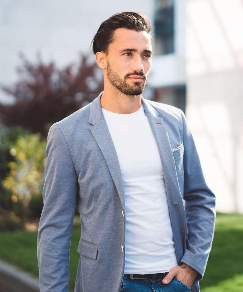 תמונה של דוגמן עם חולצה לבנה וזקט מצטלם לאתר 131 עיצוב שיער